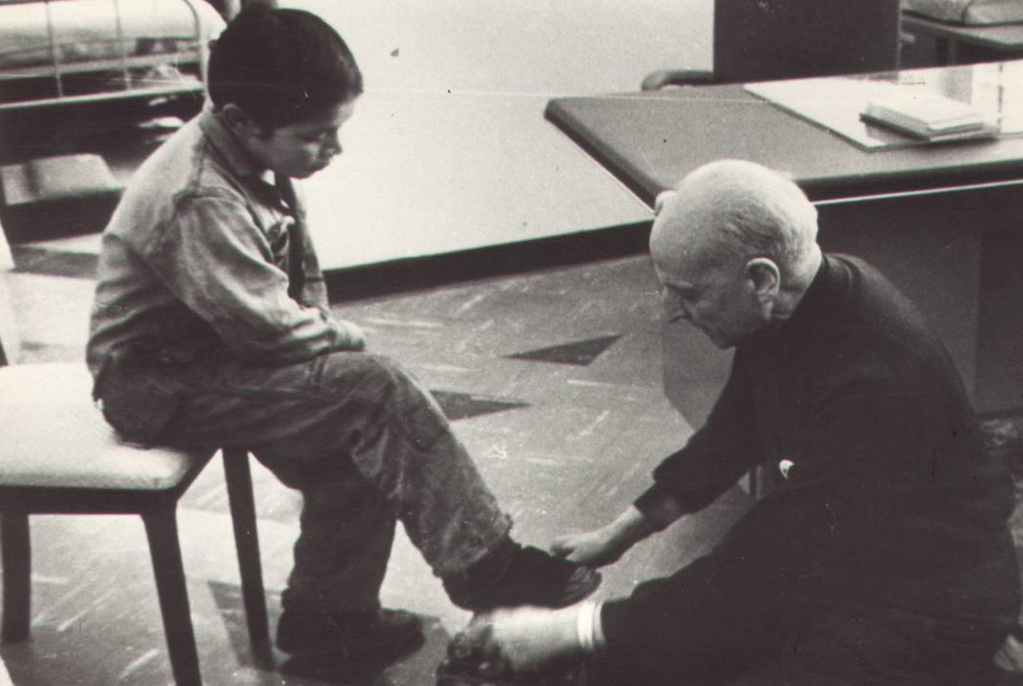 Fr Pedro Arrupe SJ shining shoes for a children in Quito, Ecuador in 1971.