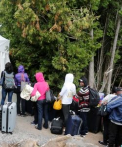 A line of asylum-seekers who said they were from Haiti wait to enter into Canada from Roxham Road in Champlain, New York, Aug. 7, 2017.