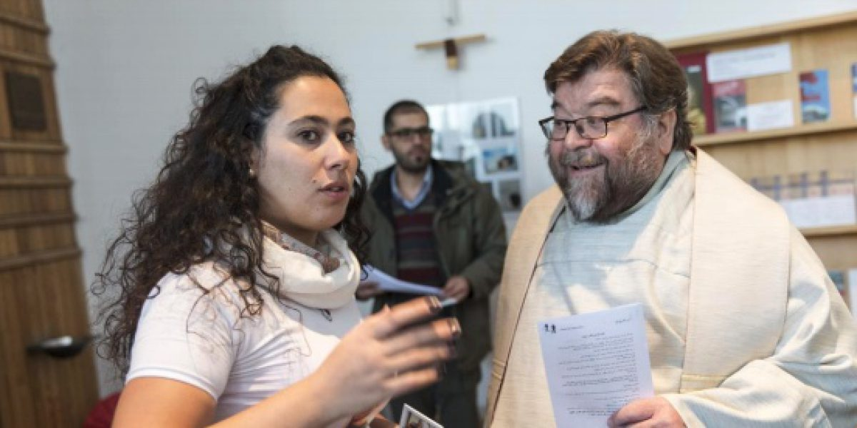 A refugee from Syria speaks with Fr Frido Pflüger SJ, former JRS Germany Country Director, about a community event she's helping to organise.
