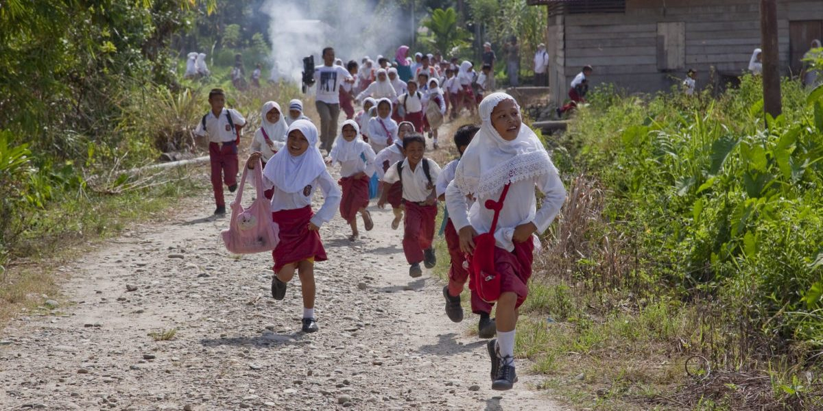 Children run during a simulation of an emergency evacuation organised by the JRS Disaster Preparedness teams in the village of Lawe Sawah, Indonesia.