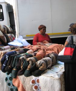 Sr. Joanne Whitaker and the JRS IGA project director speak with Martha, a Ugandan refugee woman from JRS IGA program, who markets her hand sewn pillows and spreads on street in Johannesburg, South Africa, March, 2010.