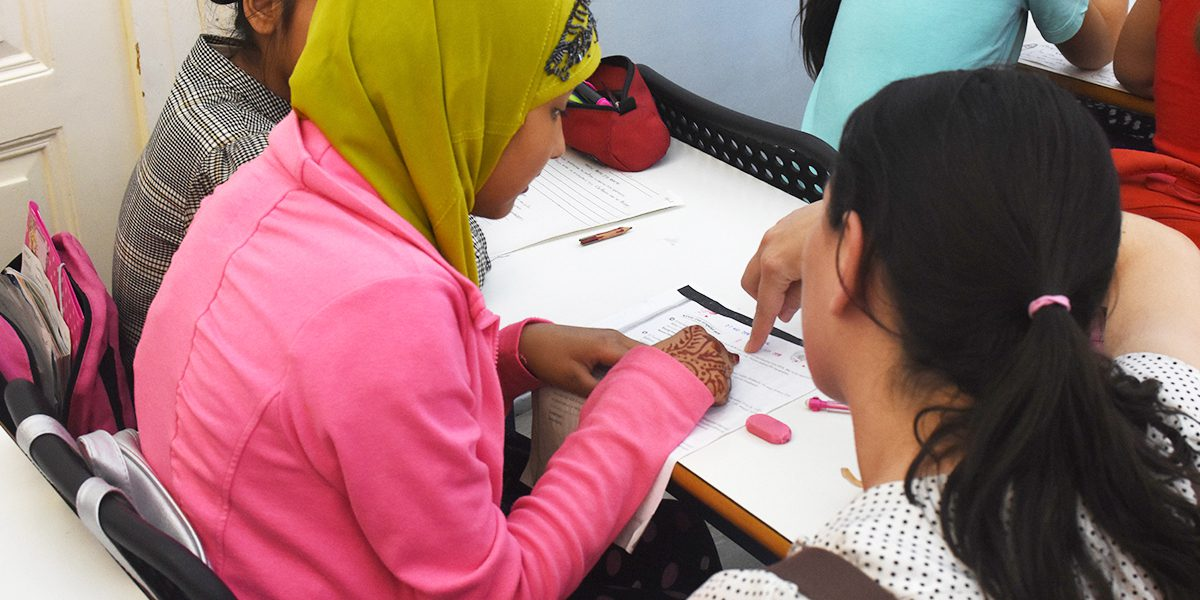 A young woman gets help from a teacher on her class assignment at the Arrupe Center in Athens.
