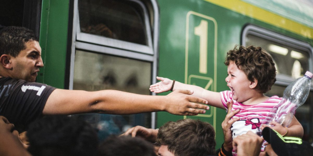 From a train, this man, between tears and rage, tries to touch his child.