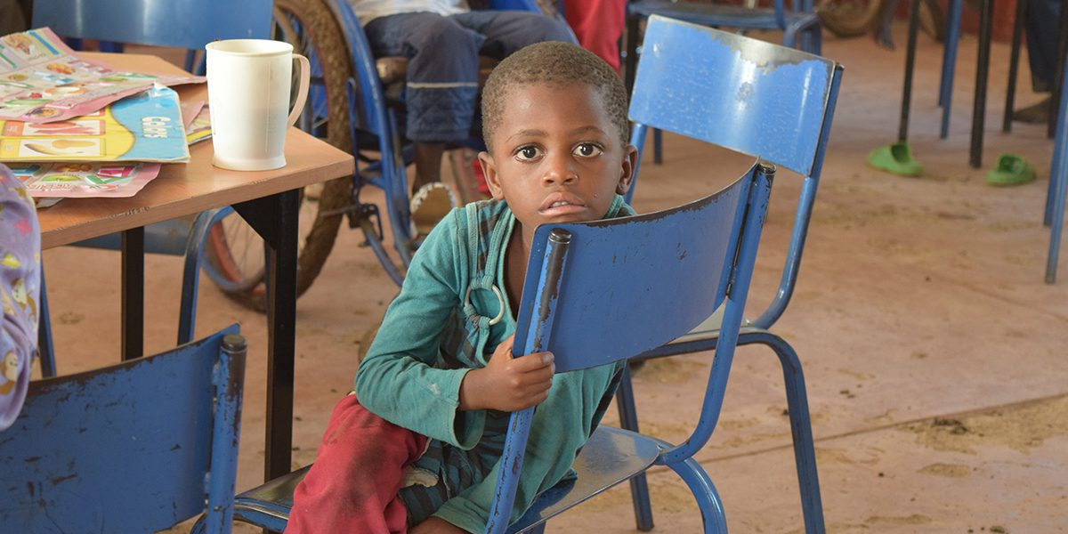 A student stares into the camera as he sits sideways on his chair in class.