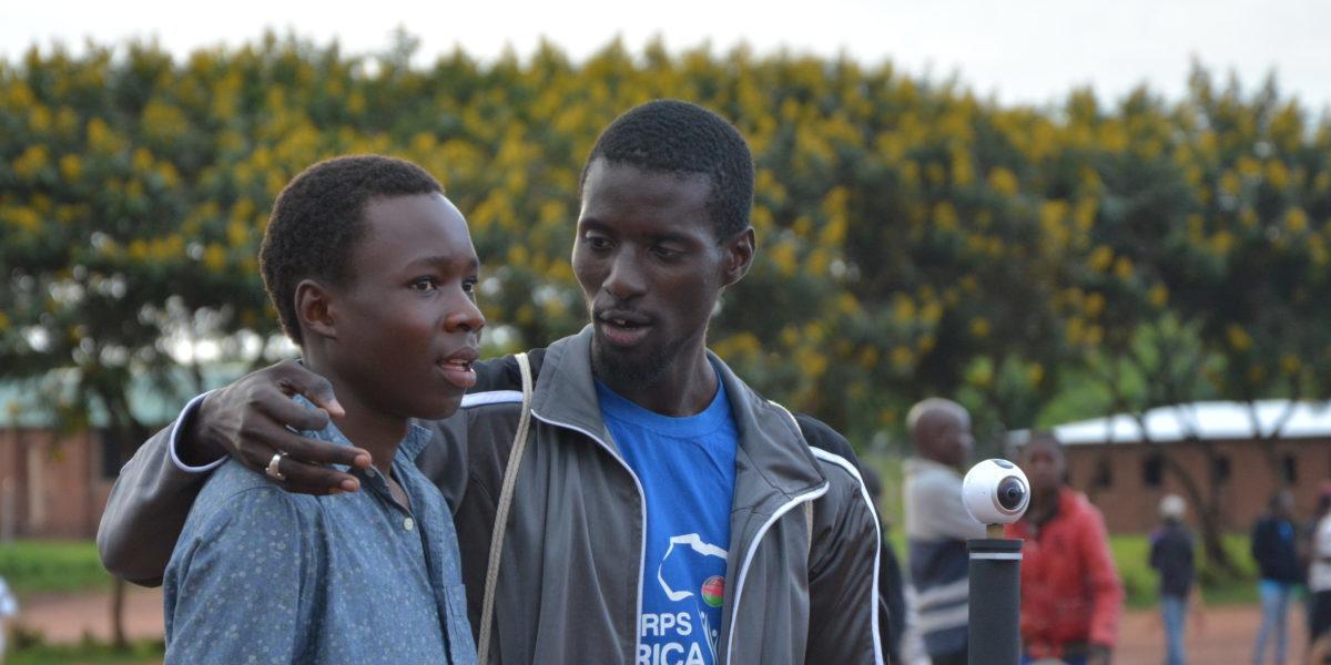 Dos refugiados se toman un descanso durante un partido de baloncesto en el campamento de refugiados de Dzaleka. (Servicio Jesuita a Refugiados)